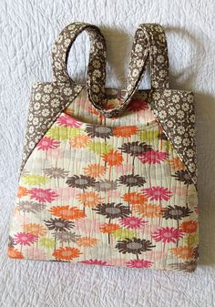 Tote bag pattern for a spacious bag with deep front pocket and zippered pocket on the back; 3 sizes are included.
