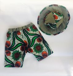 Here is a unique African wax cotton print baby girl's green and orange shorts and matching cap set.   Perfect for sunny days.