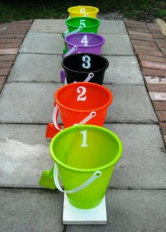 Let the kids throw things into the buckets... (Plastic novelty toys or balls get them at the dollar store)  then add up the numbers on the buckets that they actually got something in. The one with the highest numbers wins the game.