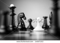 white pawn surrounded by black chess pieces on a chess board - stock photo