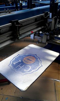 We mist a fine layer of glue onto the presses to hold the t-shirt in place when we print. Sometimes the ink and shirt fuzzies stick a bit leaving an imprint.