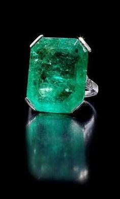 An art deco emerald ring, circa 1920 The step-cut emerald, weighing 19.15…