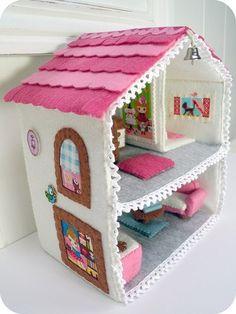 Una casa de muñecas hecha con cajas de cartón y forrada con fieltro.