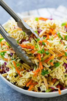Ramen noodle salad with tongs scooping it out.
