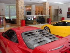 awesome garage, I like the stacked stone columns with the contemporary furniture (and the Ferrari)