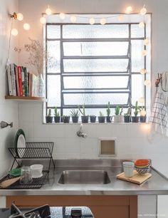 Janela de cozinha antiga de cordão de luz e vasinhos com cactos.