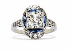 Chelsea is an amazing vintage Art Deco engagement ring featuring a 1.51ct Old European Cut diamond bordered by bright blue sapphires in a diamond encrusted oval halo. Stunning! TrumpetandHorn.com | $17,850