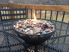 """Create an outdoor """"Rock Candle"""" with a wire basket/bowl, empty glass jar filled with Tiki torch fuel, wick inserted through a hole in the jar cover and a collection of rocks surrounding and covering the jar. Sit back and enjoy! Created by: Karla Reichel"""