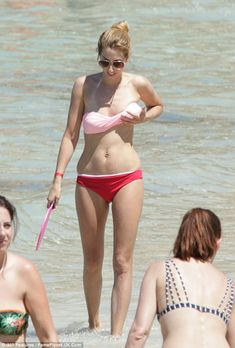 Keeping things in check: Stacey Solomon adjusts her bikini top as she holidays in Ibiza earlier this month
