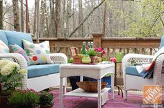 Deck Decorating Ideas: A colorful backyard deck with white wicker patio furniture and a pink outdoor rug