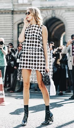 Elena Perminova wears a cut-out polka-dot high-low dress, mini Dior bag, round sunglasses, and patent leather Dior boots