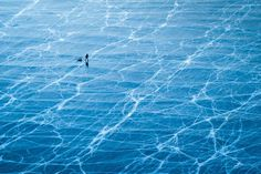 I took this shot from a mountain on Olkhon island at lake Baikal, Russia. This man was walking on the frozen lake in winter looking for fresh water by drilling through the ice. I captured this scene in order to show this unbelievable large and beautiful frozen lake.