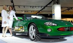 """Two Bond Girls show off the Jaguar XKR used by villain Zao in the 2002 movie """"Die Another Day"""" at the 2002 James Bond Cars Motor Show in Bir..."""