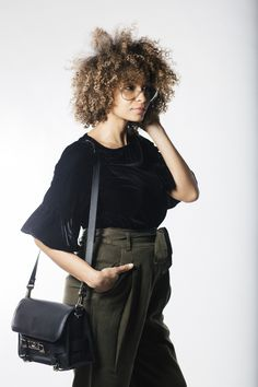 The modern work style in velvet blouse and fabric trousers plus a leather shoulder bag