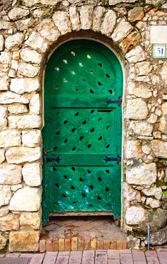 Old green door in Capri, Italy surrounded by stone work.