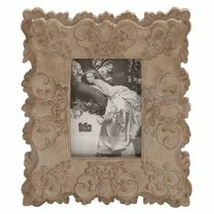 """Picture frame with a scrolling garland motif.     Product: Picture frameConstruction Material: PolystoneColor: NaturalFeatures: Holds (1) 4"""" x 6"""" photoDimensions: 11"""" H x 9"""" WCleaning and Care: Wipe with dry cloth"""