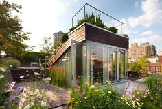 New York, Manhattan    Greenwich Village rooftop garden.Sustainably harvested Ipe decking covers this enormous space, framed by gardens of wildflowers, herbs and birch trees giving the ultimate in privacy from all angles. There is a full stainless steel k