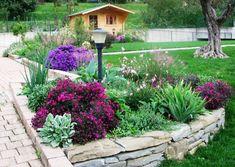 Muretto a secco, aiuola e bordura mista con erbacee perenni in fiore in ottobre: creazione giardini + casetta