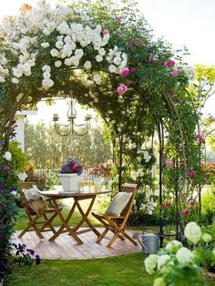 Arbor of blooming Roses above a cute little Cafe Table and 2 chairs - leads to a Garden Paradise !