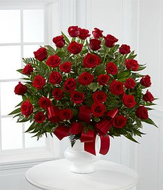 The Soul's Splendor Arrangement is a rich display of the love shared throughout the life of the deceased. Brilliant red roses are elegantly displayed in a white designer plastic urn and accented with lush greens and red satin ribbon