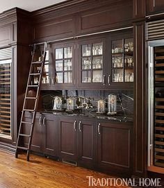 Rich brown cabinets boast plenty of storage space. A fun sliding ladder ensures access to hard-to-reach places. - Traditional Home ® / Photo: Werner Straube / Design: Megan Winters Apartment Kitchen, Kitchen Interior, New Kitchen, Kitchen Design, Kitchen Ideas, Kitchen Racks, Kitchen Wood, Kitchen Reno, Kitchen Inspiration