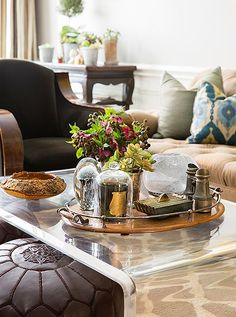 A collection of vintage trinkets and candles adorn an acrylic coffee table for a perfect mix of traditional and modern styles.