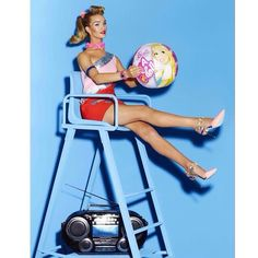 Clad in a Versace dress, Rosie Huntington-Whiteley is a Beach Barbie on a lifeguard stand.