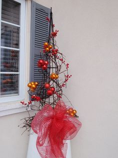 Red and copper colour Christmas ornaments wired on a obelisk to make a quick festive front porch feature.