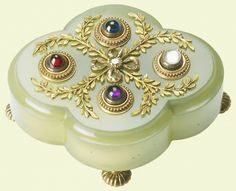 Pale green bowenite bell push of quatrefoil shape, on two-colour gold bun feet. Set with sapphire, ruby, amethyst and moonstone press studs, and mounted with sprays of foliage and central ribbon around a diamond. Faberge, c. 1900