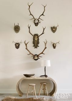 Small and large wall-mounted horns mingle to create one cohesive statement in the foyer. Console, Mrs. Howard. Stools, South of Market. Root lamp, mounted horns and beads, A. Tyner Antiques. Hide rug, Bungalow Classic.  Beth Webb Interiors - Fresh-faced Beauty | Atlanta Homes & Lifestyles