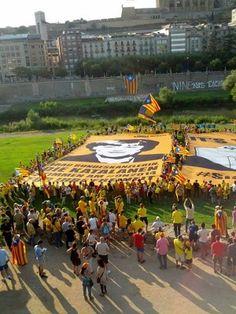 """L'ANC a Merkel: """"Senyora cancellera, el 9-N els catalans votaran per la seva llibertat"""" - elsingular.cat, 26/07/2014. Avui l'ANC ha estès a Lleida el tercer dels 10 murals que interpel·la els principals líders mundials per internacionalitzar la consulta. I l'ha dirigit a la cancellera alemanya, Angela Merkel. La frase, escrita en alemany, deia: """"Senyora cancellera, el 9-N els catalans votaran per la seva llibertat"""", acompanyada per una fotografia de Merkel."""