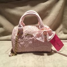 "PRICE REDUCTION Cutest PALE PINK BJ mini The cutest pale pink mini bag. Tag says Betsey heart logo blush. This bag can be held by handles or used as a cross body. It has gold hardware and the Betsey Johnson writing is in gold stitching. It has a pink ribbon and a crystal charm. The inside is signature BJ with red satin and pink lips with Pale pink leather BJ sign. This bag is a mini L: 7.5"", H5.5"", W:4"". Selling price $68 plus tax equals $74 Betsey Johnson Bags Mini Bags"