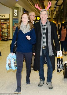 A very festive look: Clearly delighted to have her with them for the holidays, Emily's parents looked ecstatic as they walked through the travel hub with their famous daughter, her husband and their granddaughter