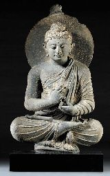 A Gray Schist Figure of Buddha;  Gandhara, circa 4th Century;  Seated in dhyanasana with his arms crossed before his chest in the gesture of teaching, dharma-chakra mudra, wearing long flowing robes draped across his left shoulder, his face with a meditative expression and wavy hair rising to a domed top-knot and backed by a nimbus.