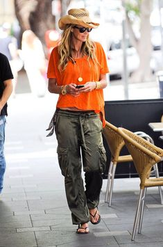 Casual chic in an orange blouse, cargo pants and black flip flops.
