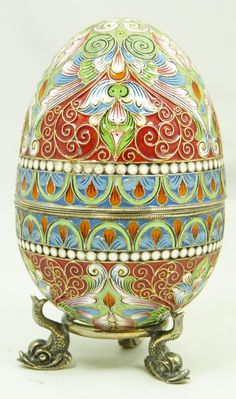 "Russian silver enameled egg box having elegant scrolled floral design. Gold wash interior. Includes stand with three figural fish feet. Piece holds Faberge marks. Holds 88 silver purity mark with Moscow town mark and workmaster mark. Holds marks to both sides of interior. Base marked 84. Measures 3 1/2"" height + 1/2"" base height (8.9cm x 1.2cm). Total weight of 5.93oz"