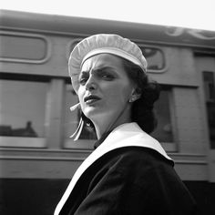 An unhappy woman with a white beret and a bus behind. September, 1956, New York…