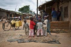 Niños ruandeses juegan junto a una procesadora de nueces en el refugio de Nakivale, en Uganda. (AP)