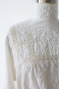 Edwardian cotton blouse featuring high neckline, broderie anglaise needlework with lace inserts and self covered, embroidered buttons up the back.