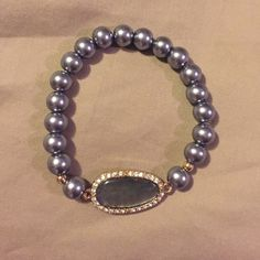 Express pearl with stone and rhinestones bracelet Blueish gray colored faux pearls with stone detail and rhinestone trim. Elastic band. Express Jewelry Bracelets