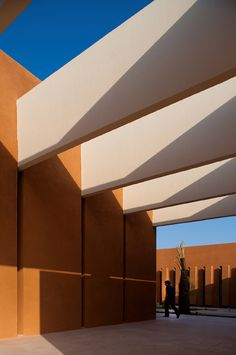 The harsh sunlight in the Moroccan desert casts dramatic shadows across the sandy red walls of this university