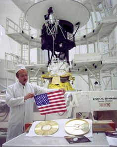 Voyager project Manager John Casani with small American flag and Golden record which are on-board both Voyager space craft. Voyager 2 is the background. This image was taken 16 days before it was launched. Credit: NASA/JPL.