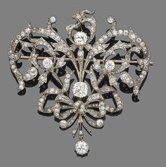 A diamond brooch/pendant The scrolling openwork cartouche highlighted with foliate and bow details, set throughout with cushion, old brilliant and rose-cut diamonds, suspending an old brilliant-cut diamond drop, diamonds approx. 6.50cts total, length 6.7cm