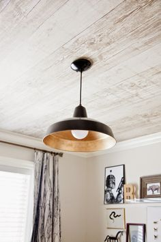 For the pendant, she added a DIY touch to this inexpensive light from Home Depot. What looks like wood planks on the ceiling is actually wallpaper from eBay.