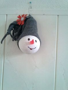 Sneeuwman gemaakt van een gloeilamp en een oude sok als muts.: