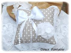 Coussin dalliances confectionné dans un tissu couleur taupe à pois blanc bordé dune jolie dentelle anglaise ton sur ton blanc à motif fleuri. Le coussin est garni dune fleur réalisée en tissu blanc et effiloché ainsi que dun noeud en satin blanc avec deux rubans organza blanc