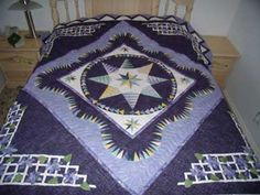 """Stardust: Description: The centre section of this quilt uses a paper piecing technique and was designed by Jacqueline De Jonge's design """"Pretty Purple."""" See the colour coordinated wall hanging below, too. Stardust will also look wonderful on a wall."""