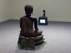 TV Buddha - Nam June Paik. (A fat, black Buddha watches television. He sits giggling before the screen, and looks like he's enjoying a show. I imagine canned laughter blaring out. But the television is silent, an empty shell. A dead candle sits in the cabinet. Another stone Buddha looks alert, attentive, transfixed before another dead TV, watching a show only he can see. You imagine his wonder at the virtual world in his head).