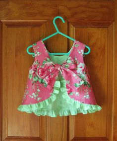 This sweet little top & ruffled bloomer set is made with a beautiful rose fabric in shades of rose/pink and green. The lining and ruffle on the top as well as the ruffles on the bloomers are done in a pretty green on green rose patterned fabric.