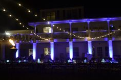 Purple uplighting makes a cool effect on the lake house for the party. | WM Events